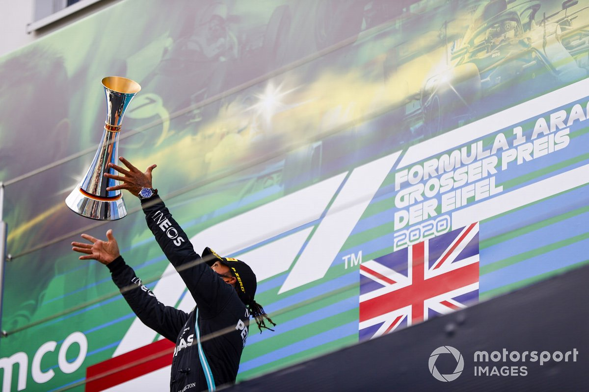 Lewis Hamilton, Mercedes-AMG F1, 1st position, tosses his trophy in the air in celebration on the podium