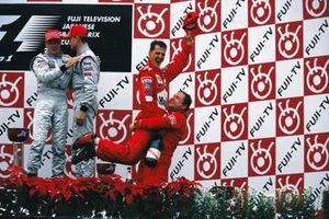 Ferrari team manager Jean Todt lifts Michael Schumacher, Ferrari, 1st position, in the air as they celebrate on the podium. Mika Häkkinen, 2nd position, and McLaren team-mate David Coulthard, 3rd position