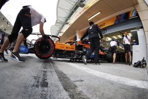 Carlos Sainz Jr., McLaren MCL35, is returned to the garage