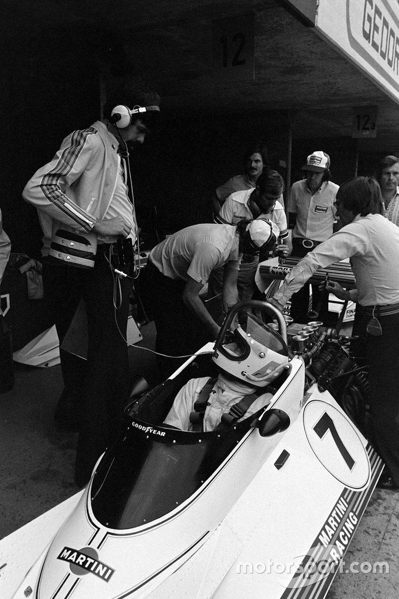 Los mecánicos trabajan en el Brabham BT44B Ford de Carlos Reutemann, mientras Gordon Murray habla con Reutemann y Bernie Ecclestone se apoya en el aro de rodamiento y observa