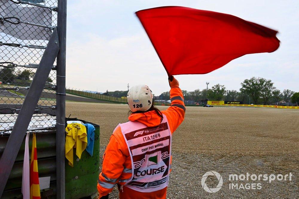 Un oficial de pista con bandera roja