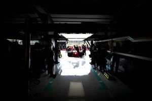 Mechanics move the car of Lewis Hamilton, Mercedes W12, into the garage