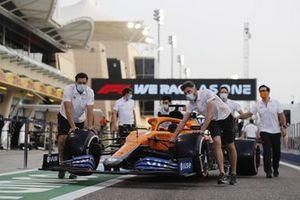 Los mecánicos empujan el McLaren MCL35M de Daniel Ricciardo en el pit lane