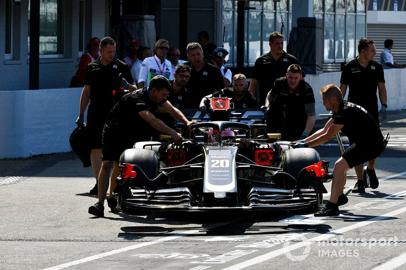 Mechanics move the car of Kevin Magnussen, Haas F1 Team VF-19