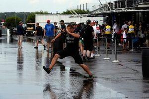 Il membro di una crew prova ad attraversare una pozzanghera a Pocono. Qualifiche cancellate per la pioggia.