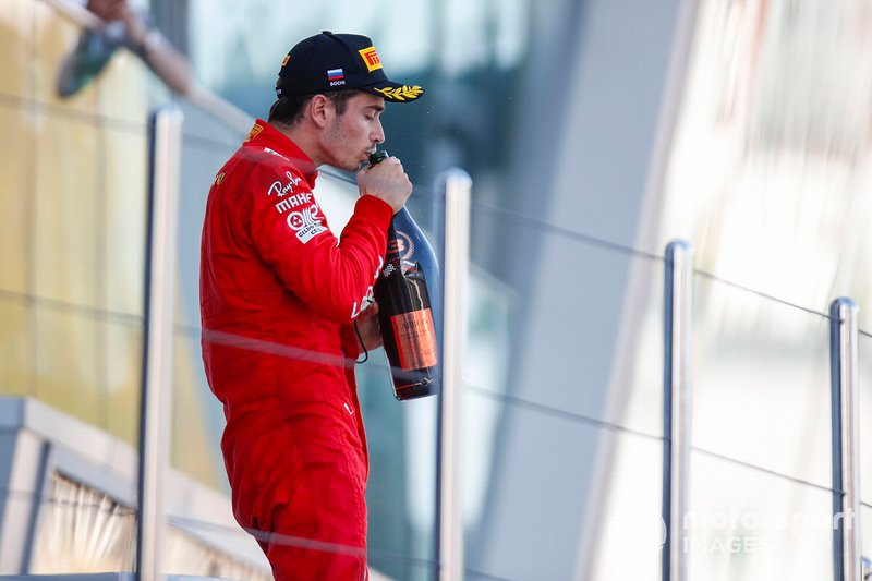 Charles Leclerc, Ferrari, drinks champagne on the podium