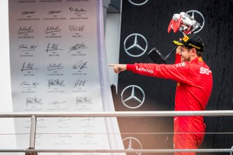 Sebastian Vettel, Ferrari celebrate on the podium with the trophy