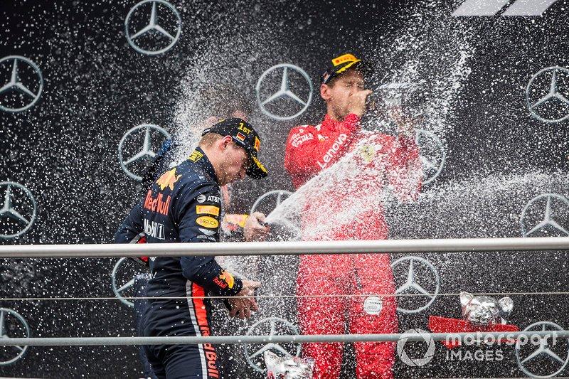 Il vincitore della gara Max Verstappen, Red Bull Racing, e Sebastian Vettel, Ferrari festeggiano sul podio con lo champagne