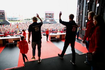 Kevin Magnussen, Haas F1 Team, and Romain Grosjean, Haas F1 Team, wave to fans from a stage