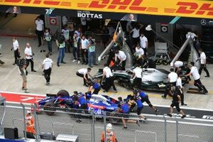 The car of Daniil Kvyat, Toro Rosso STR14, is pushed past Lewis Hamilton, Mercedes AMG F1 W10, in the pits