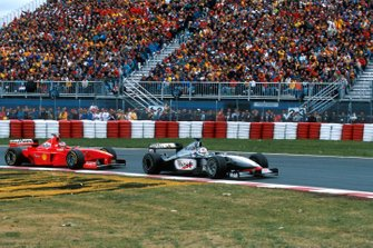 David Coulthard, McLaren MP4-13, leads Michael Schumacher, Ferrari F300