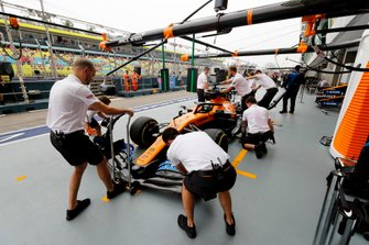 McLaren mechanics in the pit lane with Carlos Sainz Jr., McLaren MCL34