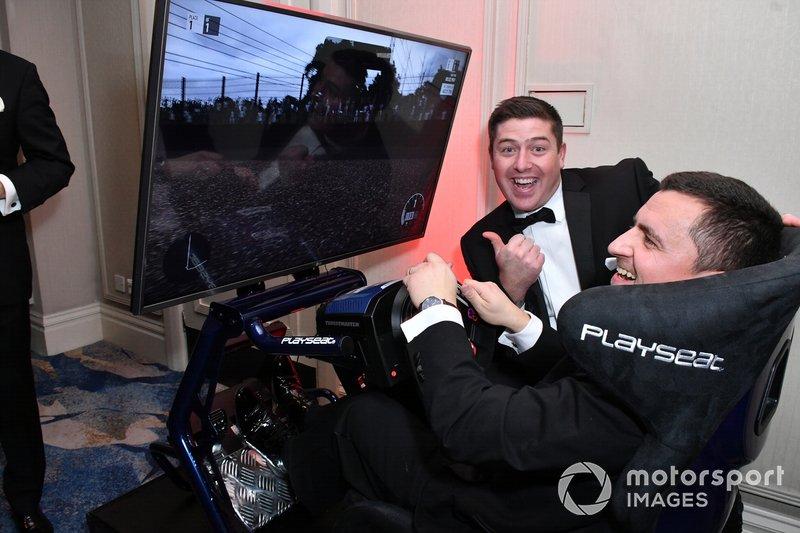 Algunos invitados prueban un simulador de carreras