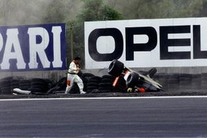 A marshal attends to Ayrton Senna, McLaren MP4-6 Honda, who has spectacularly rolled over at the Peraltada corner