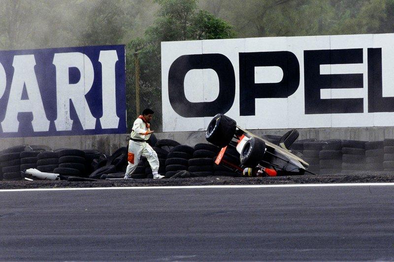Un comisario atiende a Ayrton Senna, McLaren MP4-6 Honda, tras volcar en la Peraltada