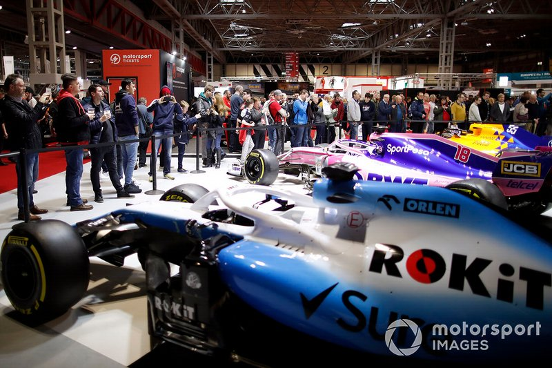 Fans admire the cars on the F1 Racing stand