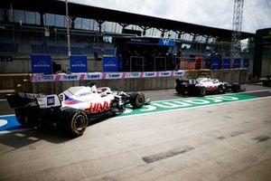 Mick Schumacher, Haas VF-21, and Nikita Mazepin, Haas VF-21, leave the garage