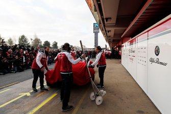 Alfa Romeo Racing mechanics with the new Alfa Romeo Racing C38 under covers