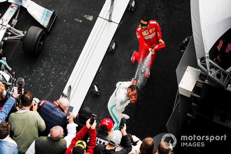 Lewis Hamilton, Mercedes AMG F1, vincitore, e Sebastian Vettel, Ferrari, terzo, spruzza lo champagne sul podio