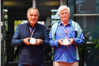 Giorgio Piola and Roger Benoit, having attended the most of the 1000 F1 Grands Prix, present the official F1 1000 coin