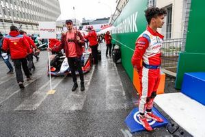 Pascal Wehrlein, Mahindra Racing, stands on a kerb near his M5 Electro which is on the grid