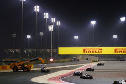 Marshals remove the car of Daniel Ricciardo, Red Bull Racing RB14 Tag Heuer, as Carlos Sainz Jr., Renault Sport F1 Team R.S. 18, Marcus Ericsson, Sauber C37 Ferrari, Lance Stroll, Williams FW41 Mercedes, and Romain Grosjean, Haas F1 Team VF-18 Ferrari, pass