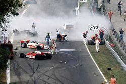 Mentre i corridori davanti imboccano la chicane del Rettifilo alla partenza della gara, un denso pennacchio di fumo nero oscura il circuito mentre un vasto incidente decima gran parte del gruppo