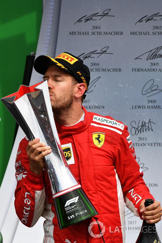 Race winner Sebastian Vettel, Ferrari celebrates on the podium and kisses the trophy