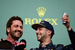 (L naar R): Gerard Butler, acteur, op het podium met Daniel Ricciardo, Red Bull Racing