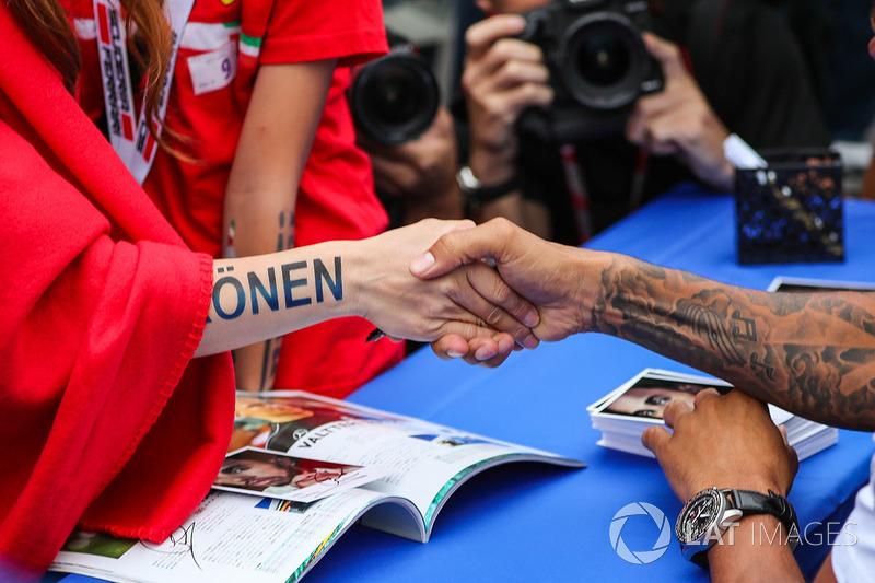 Lewis Hamilton, Mercedes AMG F1, shakes hands with a Kimi Raikkonen fan