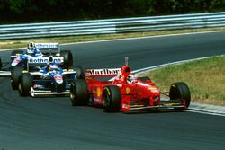 Michael Schumacher, Ferrari F310B leads Jacques Villneuve, Williams