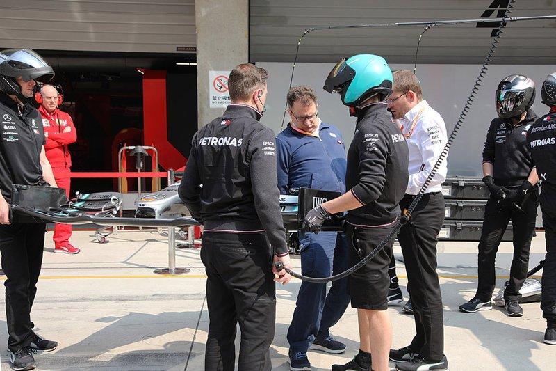 Asa da Mercedes com os membros da equipe... sob o olhar de um membro da Ferrari