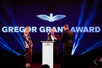 Martin Brundle presents a Gregor Grant Award on stage