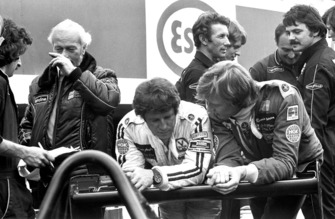 Mario Andretti and Ronnie Peterson talk in the pit lane with team boss Colin Chapman, Lotus