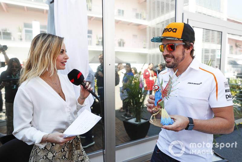 Fernando Alonso, McLaren, holds an Alebrijes sculpture while being interviewed