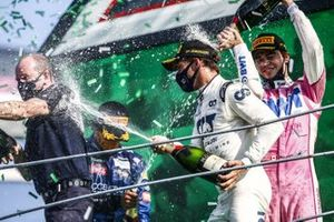 Pierre Gasly, AlphaTauri, 1st position, sprays champagne on the podium with Lance Stroll, Racing Point, 3rd position, and Carlos Sainz Jr., McLaren, 2nd position