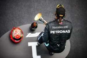 Lewis Hamilton, Mercedes-AMG F1, 1st position, on the podium with his trophy and the helmet of Michael Schumacher