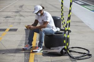 Lewis Hamilton, Mercedes-AMG F1, on his phone in the pit lane