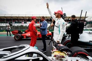 Lewis Hamilton, Mercedes AMG F1, waves to his home fans as Charles Leclerc, Ferrari, is interviewed by David Coulthard, Channel 4 F1, on the grid after Qualifying