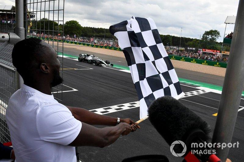 Il rapper Stormzy sventola la bandiera a scacchi, mentre Lewis Hamilton, Mercedes AMG F1 W10, taglia il traguardo