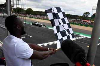 Le rappeur Stormzy, agitant le drapeau à damier tandis que Lewis Hamilton, Mercedes AMG F1 W10 franchit la ligne d'arrivée