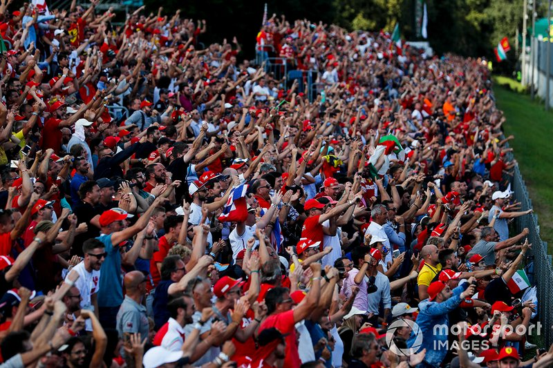 Fan esultano mentre Charles Leclerc, Ferrari, difende il comando