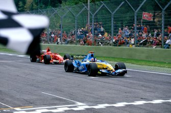 Race winner Fernando Alonso, Renault R25, takes the chequered flag, followed by Michael Schumacher, Ferrari F2005