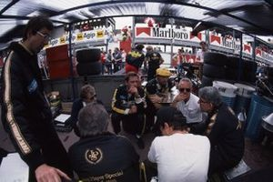 Ayrton Senna and Elio de Angelis listen to a brief by Lotus team boss Peter Warr