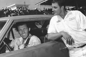 Richard Petty is seated in his racecar as brother Maurice visits