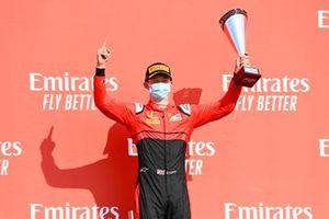 Callum Ilott, UNI-Virtuosi, celebrates victory with his trophy on the podium