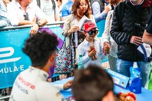 A young fan waits to meet the drivers at the autograph session