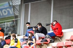 Fans take photos from a grandstand