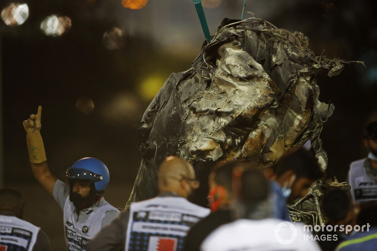 The charred wrecked remains of the Romain Grosjean Haas VF-20 is cleared by marshals after a horrendous opening lap crash at the Bahrain Grand Prix