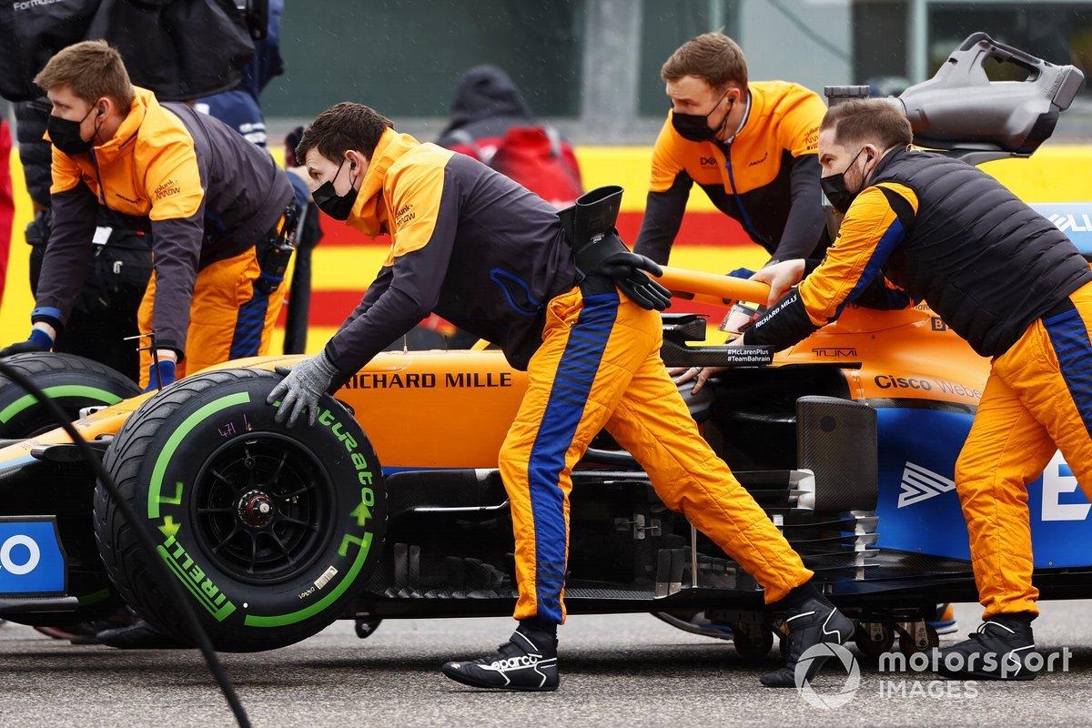 Los mecánicos empujan el coche de Lando Norris, McLaren MCL35M, en la parrilla de salida